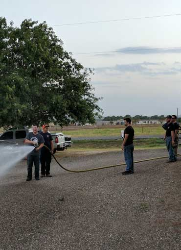 Volunteers practicing with the nozzle